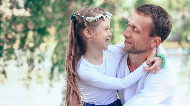 Gelukkige vader en dochtertje elkaar knuffelen in het park op een zonnige dag