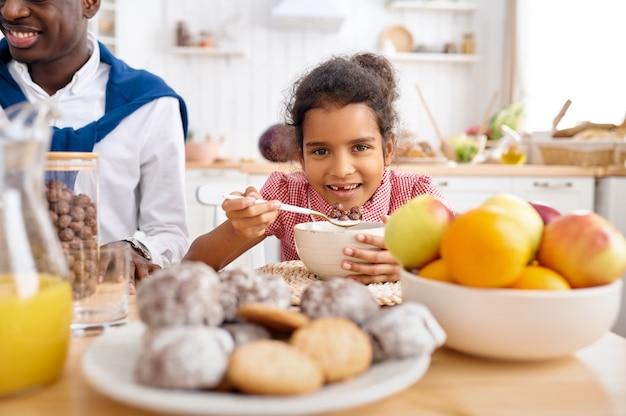 Gelukkige vader en dochtertje eten vlokken bij het ontbijt. glimlachende familie eet 's ochtends in de keuken. vader voedt vrouwelijk kind, goede relatie
