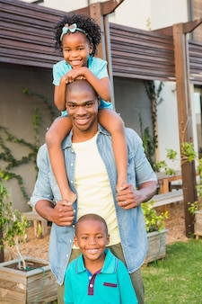 Gelukkige vader en kinderen in de tuin