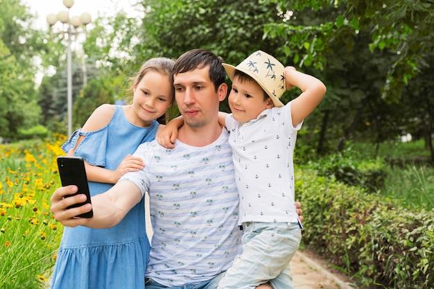 Gelukkige vader en kinderen nemen selfies.
