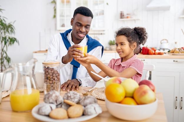 Gelukkige vader en klein kind drinken vers sap bij het ontbijt. glimlachende familie eet 's ochtends in de keuken. vader voedt vrouwelijk kind, goede relatie