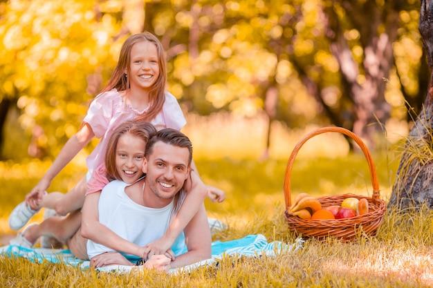 Gelukkige vader en kleine dochters ontspannen bij het meer