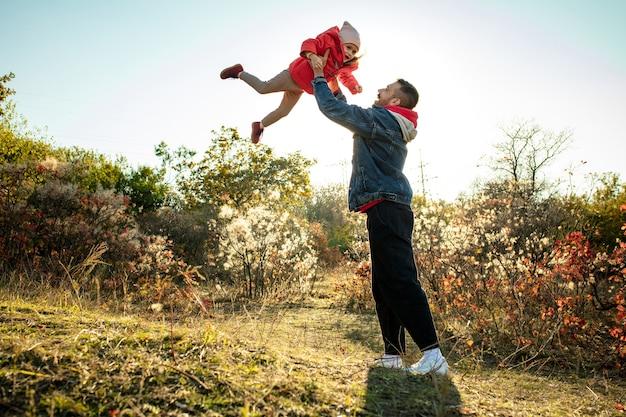 Gelukkige vader en kleine schattige dochter lopen over het bospad in zonnige herfstdag