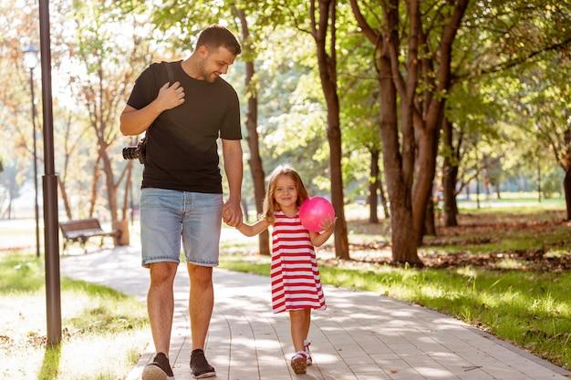 Gelukkige vader en meisje lopen in de hand houden in het park van de zomer