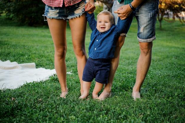 Gelukkige vader en moeder die een babyjongen houden met en op het gras lopen