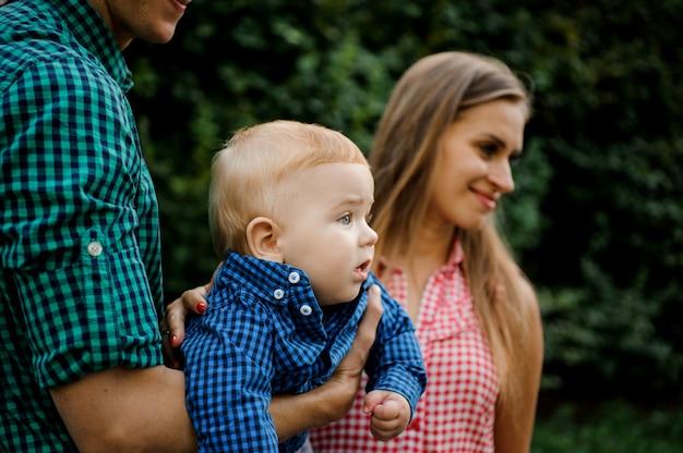 Gelukkige vader en moeder die op handen een babyjongen houden met