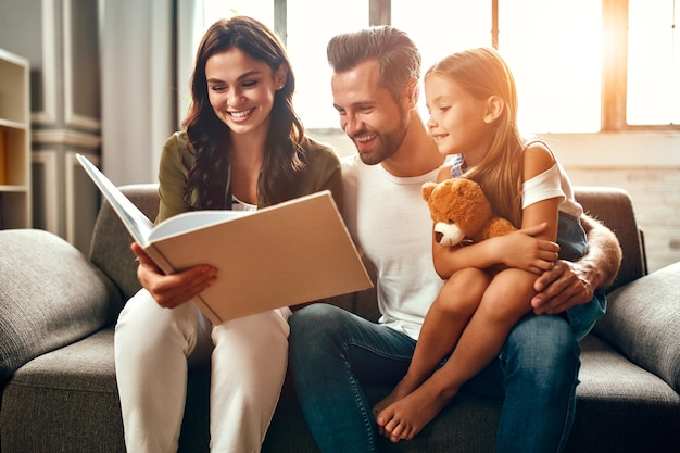 Gelukkige vader en moeder met hun schattige dochter en teddybeer lezen een boek terwijl ze thuis op de bank in de woonkamer zitten.