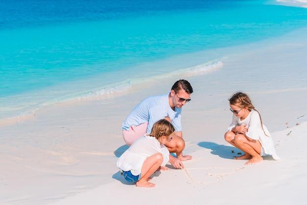 Gelukkige vader en schattige kleine kinderen op tropisch strand met plezier. familie vakantie