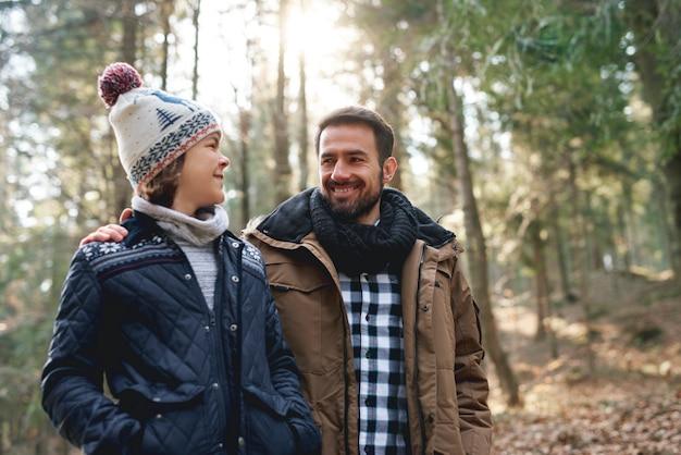 Gelukkige vader en tienerzoon wandelen in het herfstbos