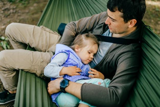 Gelukkige vader en zijn dochtertje ontspannen in een hangmat op de natuur