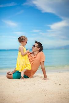 Gelukkige vader en zijn schattige kleine dochter hebben plezier op het strand