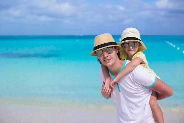 Gelukkige vader en zijn schattige kleine dochter hebben plezier op tropisch strand