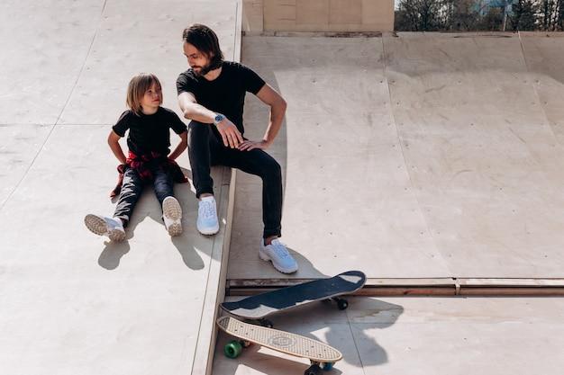Gelukkige vader en zijn zoon gekleed in de vrijetijdskleding zitten en lachen om de glijbaan in een skatepark naast de skateboards op de zonnige dag.