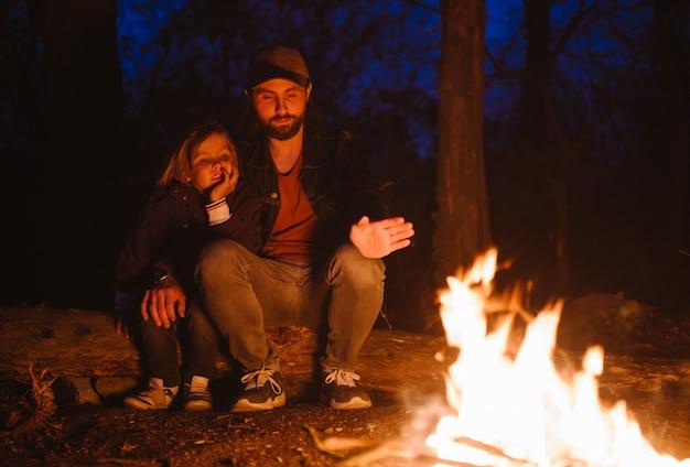Gelukkige vader en zijn zoon warmen zich 's nachts op bij het vuur terwijl ze in een omhelzing op boomstammen zitten tijdens een wandeling in het bos. .