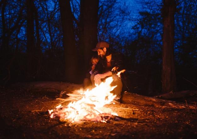Gelukkige vader en zijn zoontje zitten samen op de boomstammen voor een vuur tijdens een wandeling in het bos 's nachts. .