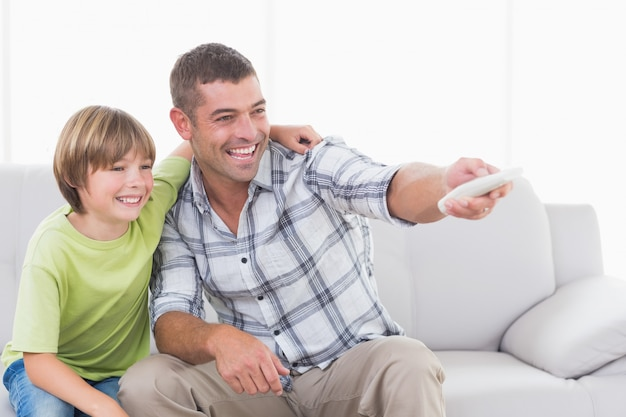Gelukkige vader en zoon die afstandsbediening gebruiken