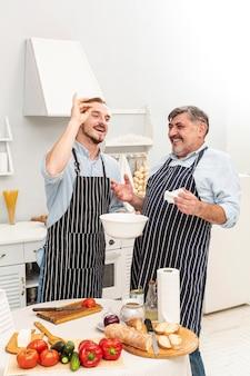 Gelukkige vader en zoon die een heerlijke maaltijd voorbereiden