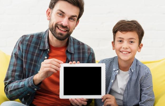 Gelukkige vader en zoon die een onechte foto houden