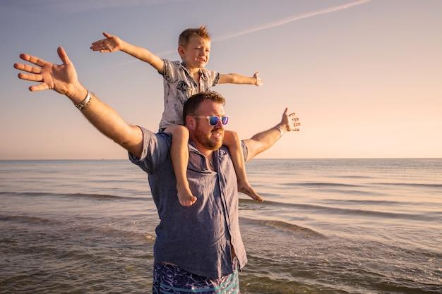 Gelukkige vader en zoon die familietijd op het strand op zonsondergang hebben