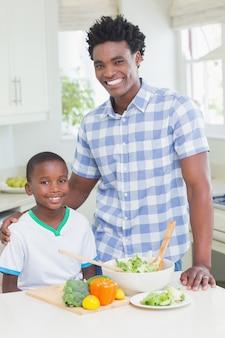Gelukkige vader en zoon die groenten voorbereiden