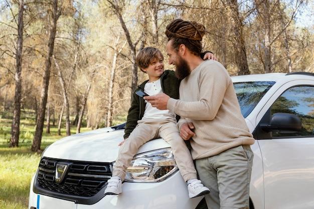 Gelukkige vader en zoon die mobiel gebruiken