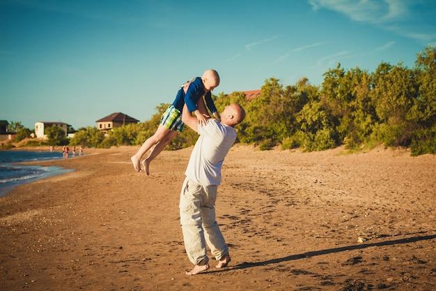 Gelukkige vader en zoon die op het strand lopen