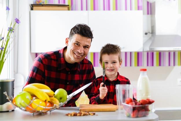 Gelukkige vader en zoon die samen gezond ontbijt maken. zittend in een keuken met mes in hun handen en camera kijken.