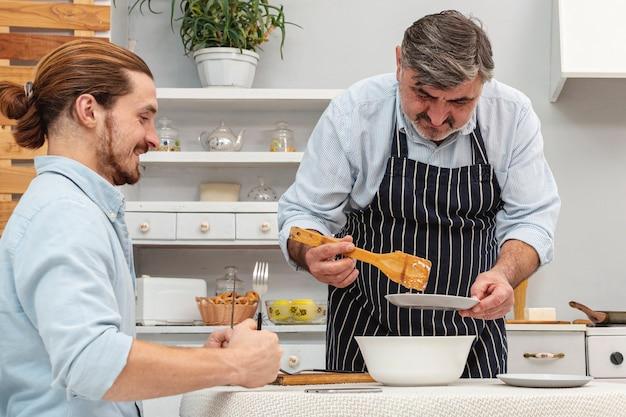 Gelukkige vader en zoon die voorbereidingen treffen te eten