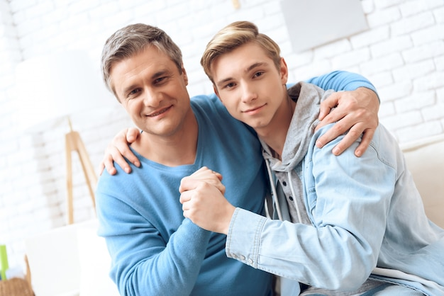 Gelukkige vader en zoon glimlachen.