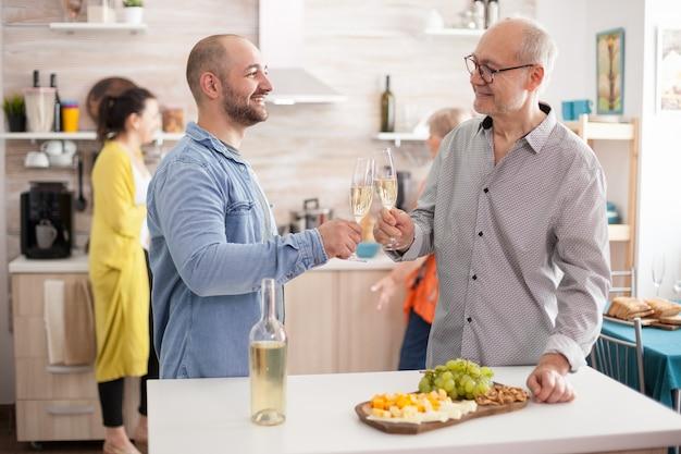 Gelukkige vader en zoon rammelende wijnglazen in de keuken tijdens de lunch met familie.