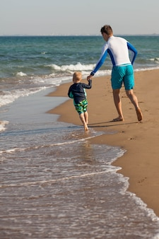 Gelukkige vader en zoon rennen blootsvoets op het strand tijd doorbrengen samen levensstijl familie cyprus kopieer ruimte