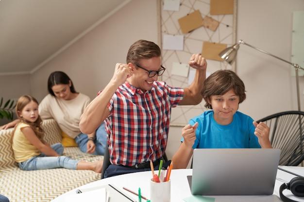 Gelukkige vader en zoon zitten thuis aan tafel en kijken naar laptop en vieren succes terwijl