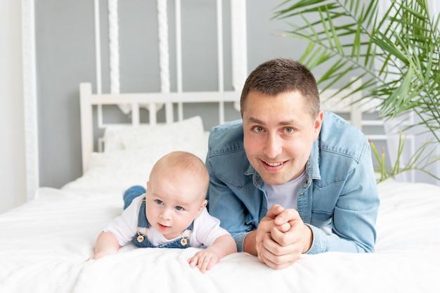 Gelukkige vader en zoontje liggen op de bank en knuffelen