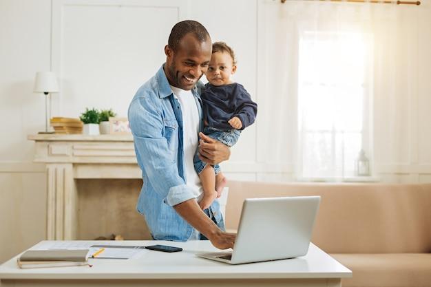Gelukkige vader. knappe geïnspireerde jonge afro-amerikaanse vader die zijn zoontje vasthoudt en op de laptop typt terwijl hij aan de tafel staat en een open haard op de achtergrond