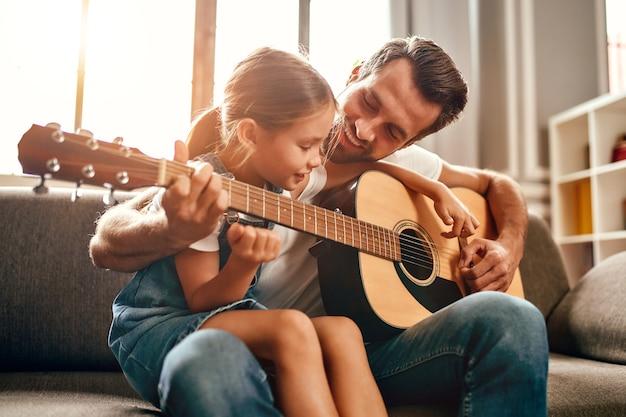 Gelukkige vader leert zijn schattige dochter gitaar spelen terwijl hij thuis op de bank in de woonkamer zit. gelukkige vaderdag.