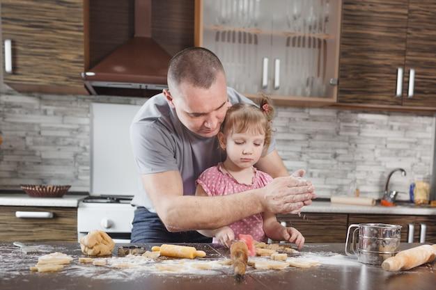 Gelukkige vader maakt koekjes met zijn dochtertje en zeeft bloem door zijn handen