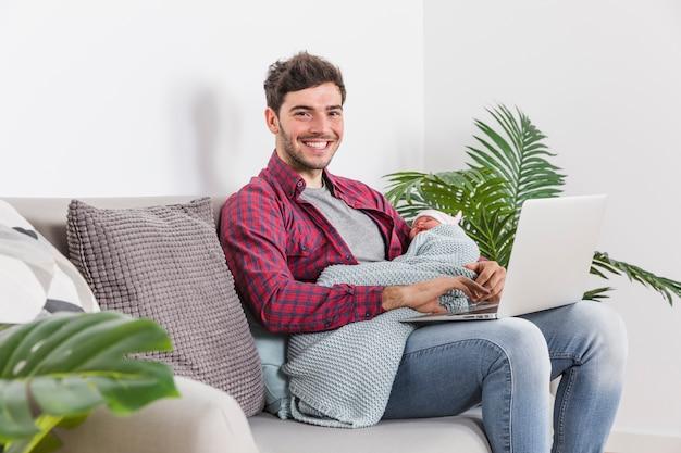 Gelukkige vader met baby die laptop met behulp van
