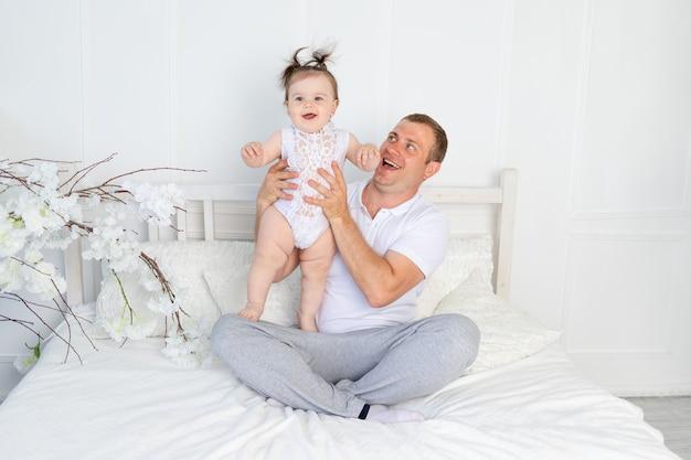 Gelukkige vader met babydochter in zijn armen op een wit bed thuis, familie