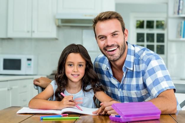 Gelukkige vader met dochter die in boek bij lijst schrijven
