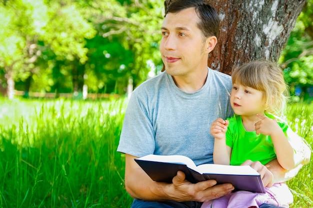 Gelukkige vader met een kind dat een boek leest over de aard van de bijbel