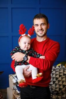 Gelukkige vader met een kind in rode truien staat samen. kerst vakantie sfeer. familie relatie concept