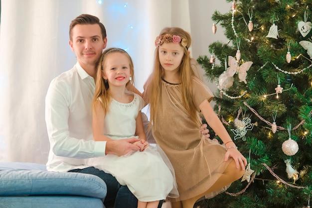 Gelukkige vader met jonge geitjes dichtbij de kerstboom op kerstmisvooravond