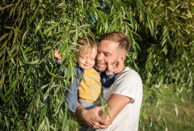 Gelukkige vader met zijn schattige zoon van de peuterjongen op zonsondergang. familie plezier en genieten van een dag in het park. vaderschap, kinderjaren en levensstijlconcept