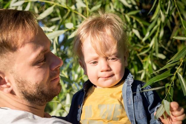 Gelukkige vader met zijn schattige zoon van de peuterjongen op zonsondergang. familie plezier en genieten van een dag in het park. vaderschap, kinderjaren en levensstijlconcept Premium Foto