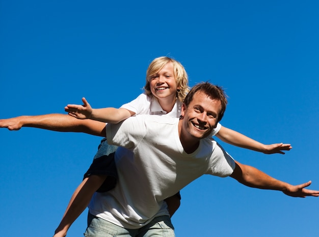 Gelukkige vader met zijn zoon op zijn rug openlucht