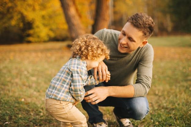 Gelukkige vader met zijn zoontje glimlachend buiten in het park bij zonsondergang, samen plezier