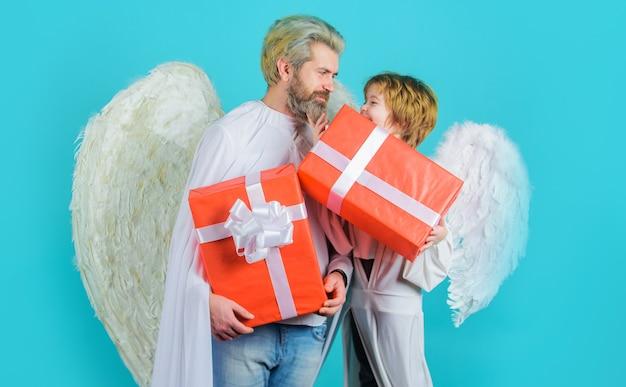 Gelukkige vader met zoon in engelenkostuum met cadeautje