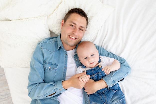 Gelukkige vader met zoontje liggend op het bed en knuffelen met plezier