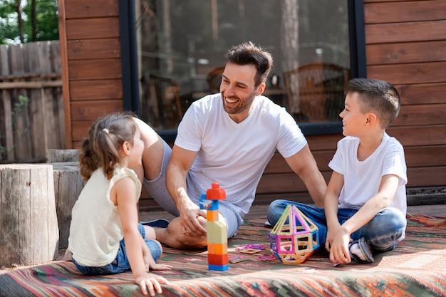Gelukkige vader of babysitter heeft plezier met klein meisje en jongen, speelt met hen in de tuin zittend op het tapijt bij het houten huis en helpt hen kinderspeelgoed te verzamelen