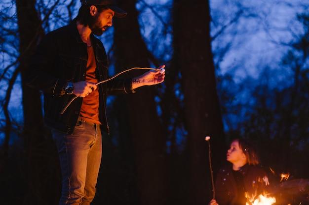 Gelukkige vader staat 's nachts voor een vuur in het bos met takjes in zijn hand. .